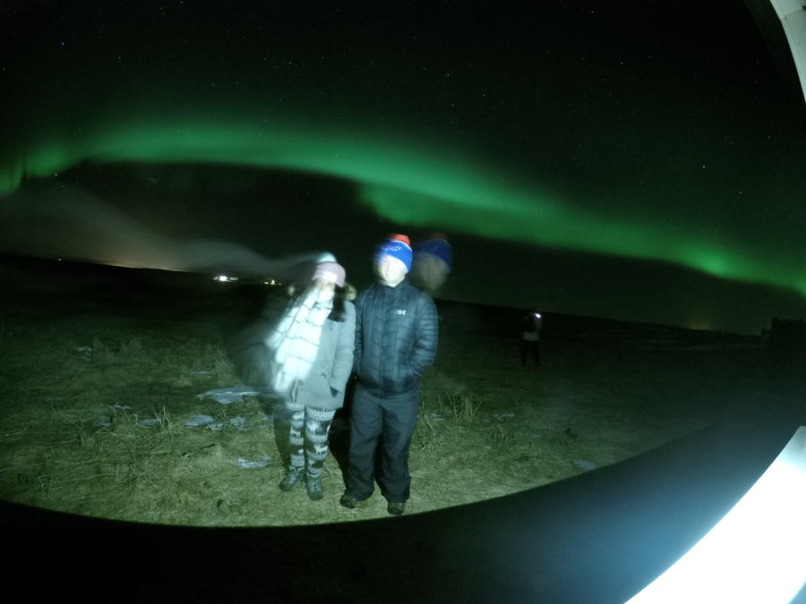Northern lights in the background of a couple posing