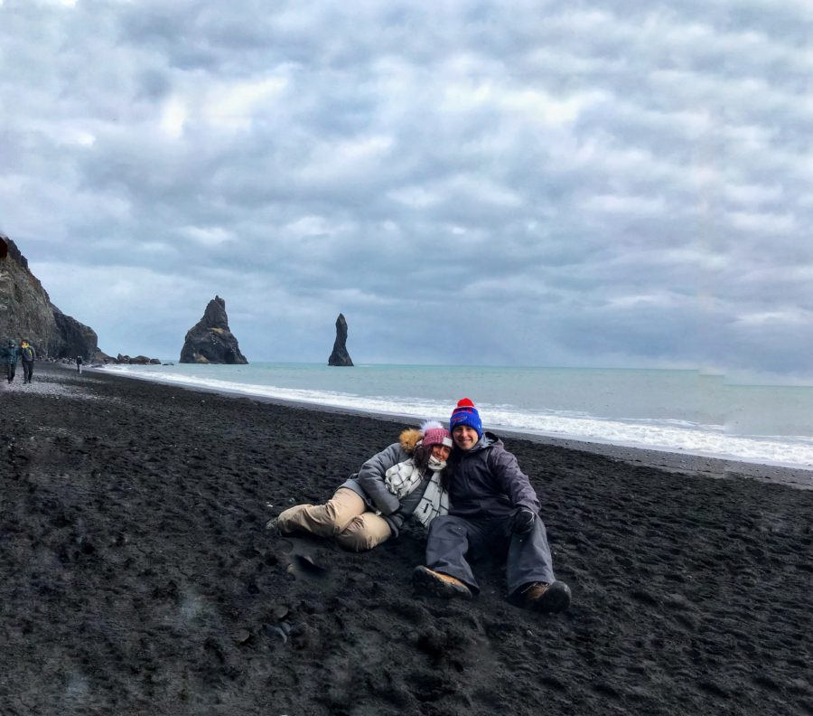 Couple sitting on Reynisfjara Black sand Beach