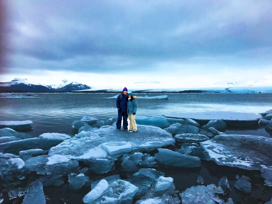 Couple standing on top of an Iceburg in Iceland