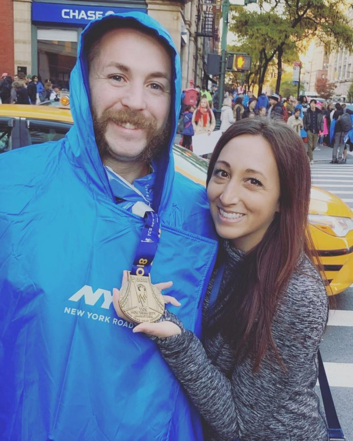 Girl holding boy's NYC Marathon Finisher Medal