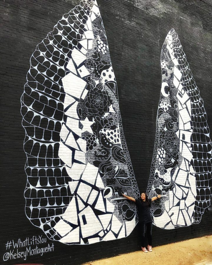 Girl posing with angel wings on a wall