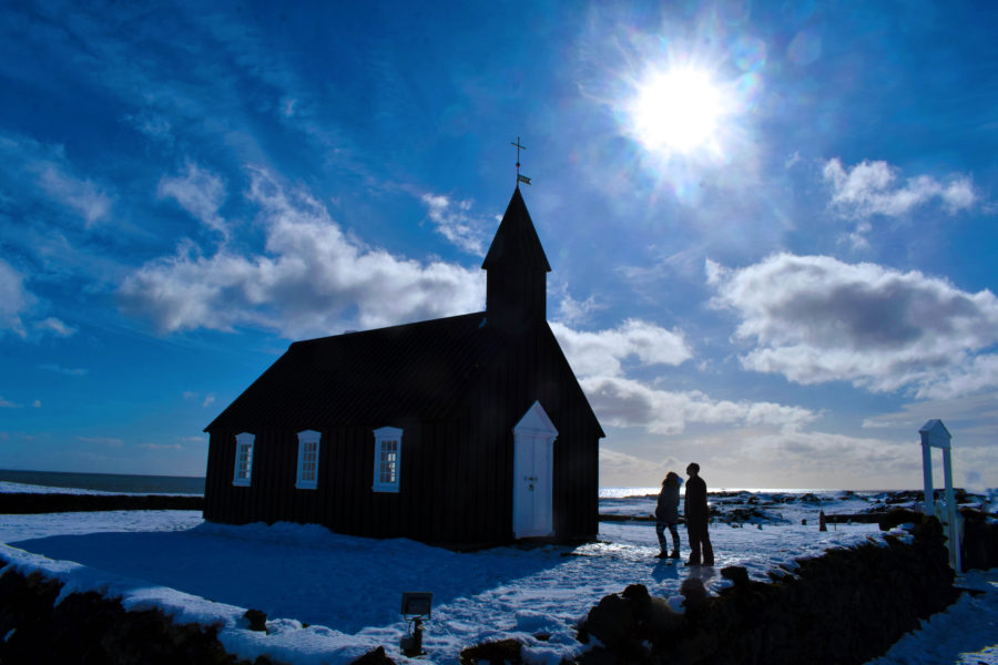 Couple admiring black church at Buðir