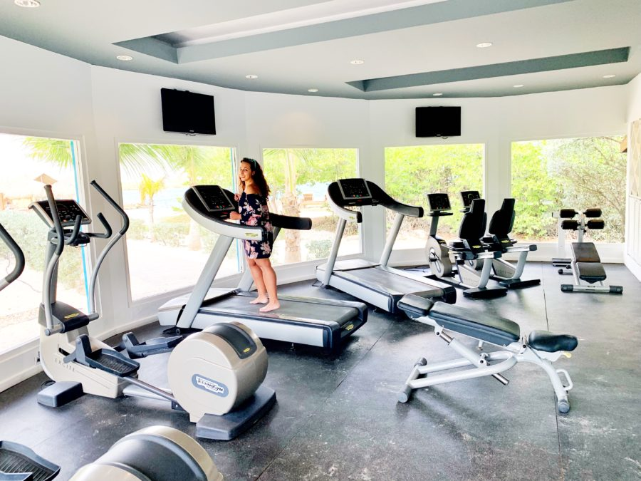 girl standing on treadmill in a gym.