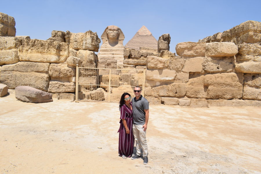 Boy and Girl standing in front of Sphinx and Pyramids of Giza