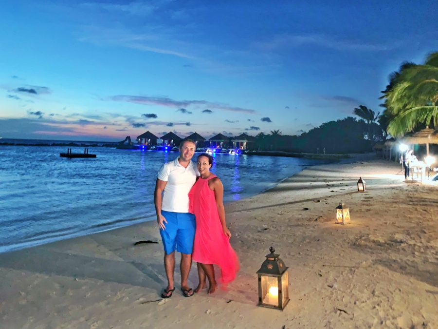boy and girl on beach as sun sets and lanterns light the beach
