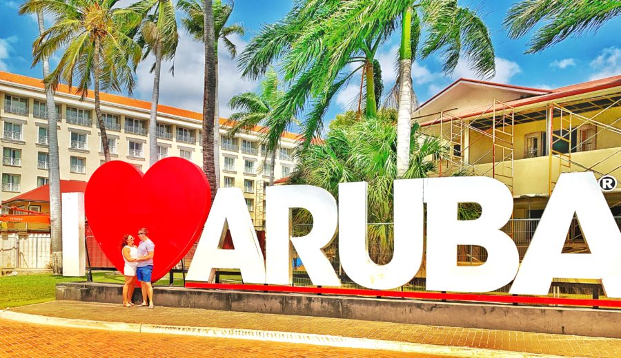 Couple posing in front of I Love Aruba Sign