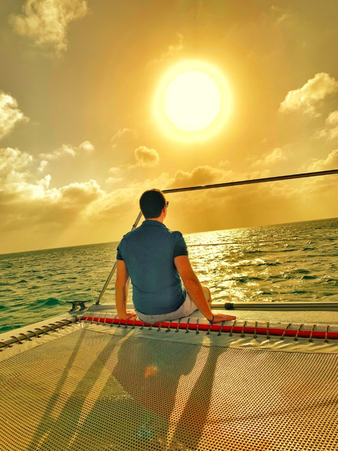 Man sitting on the edge of a boat staring into the sun and ocean