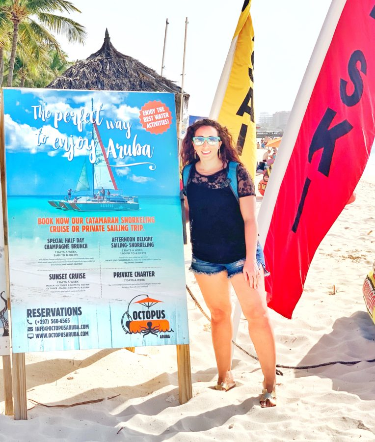 Girl standing next to Octopus Aruba Sailing sign on beach