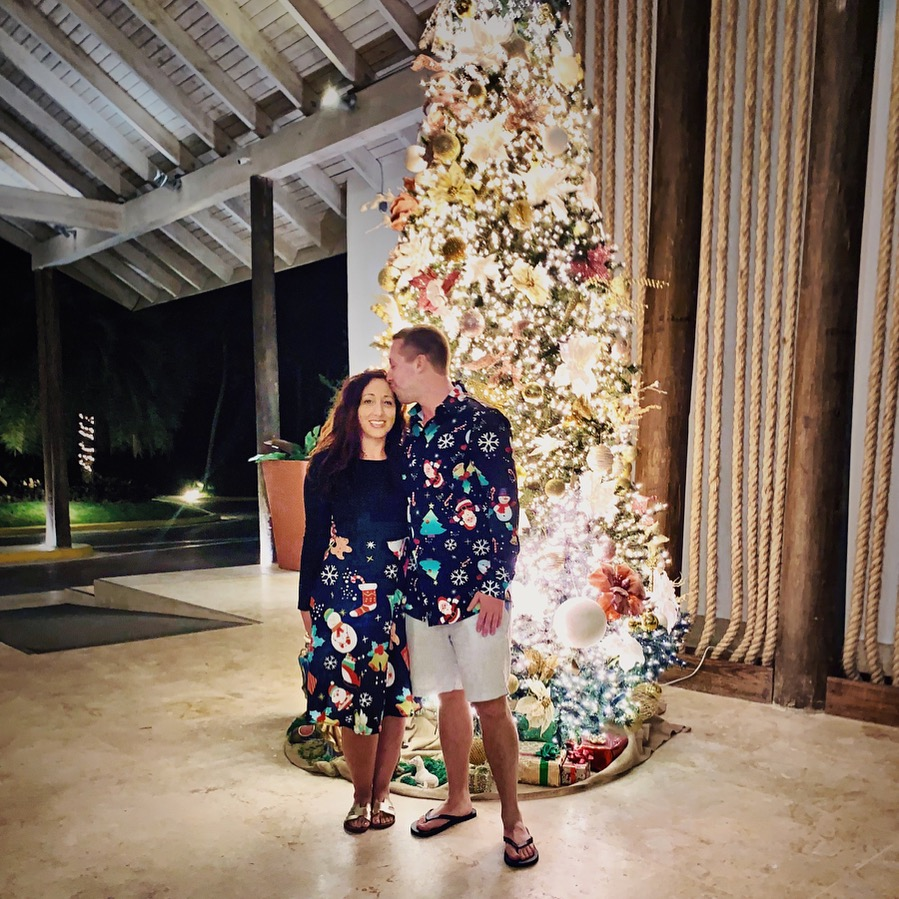Boy and girl in matching christmas outfits in front of christmas tree