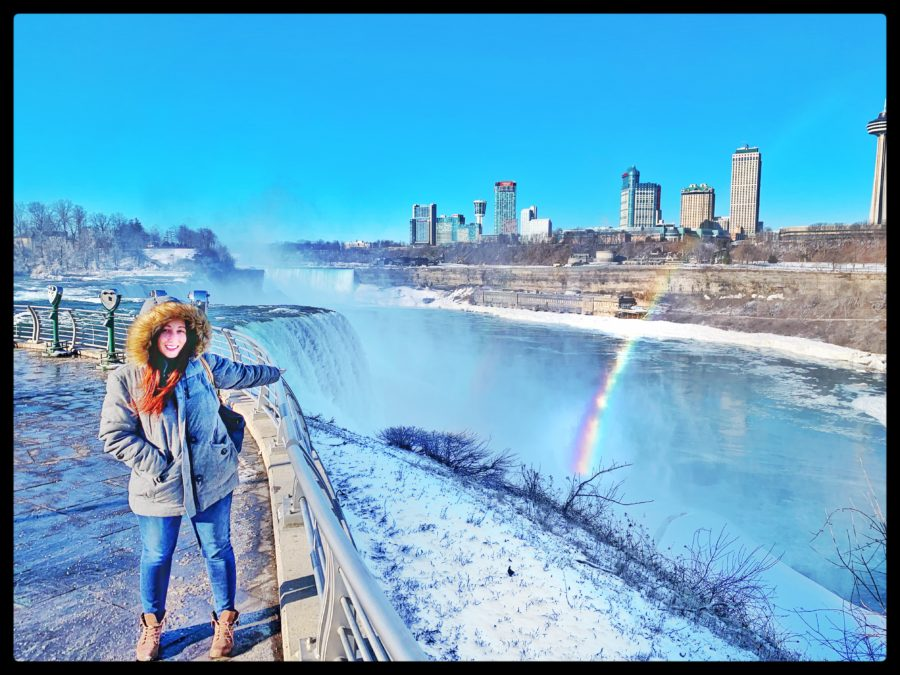 Girl standing next to Niagara Falls and a rainbow in the background