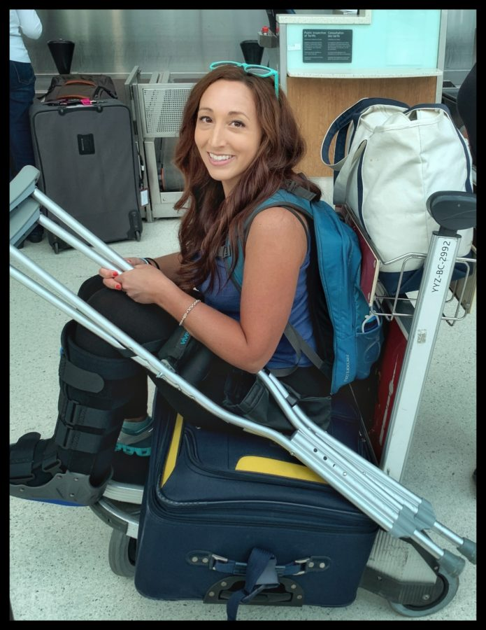 Girl sitting on a suitcase on top of a luggage cart with crutches
