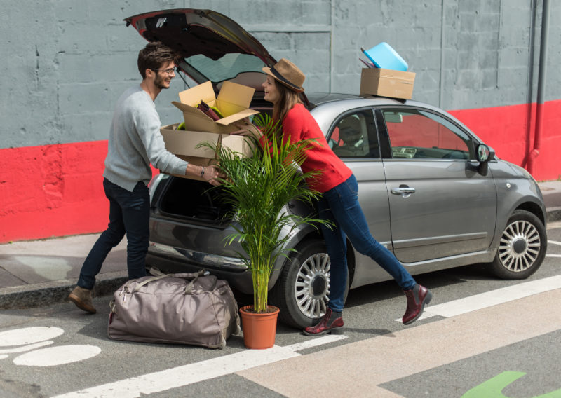 Man and woman moving boxes into car