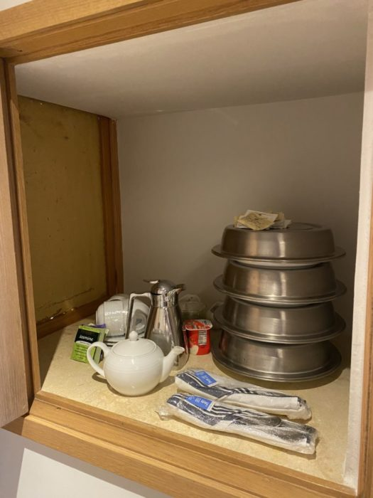 """""""Dream Box"""" in room filled with plates of food, tea and utensils."""
