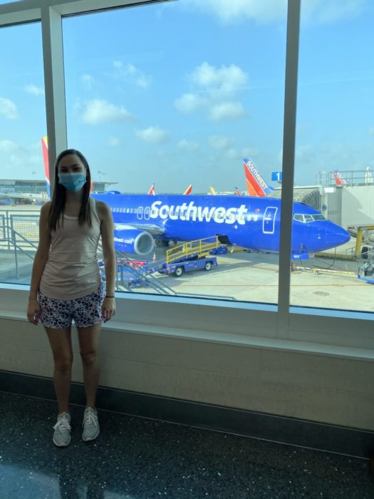 Girl with mask on and Southwest Airplane in the background