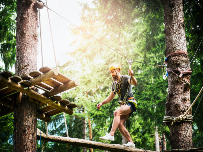 Young  bearded guy is climbing on the rope in climbing forest on beautiful nature backgrund