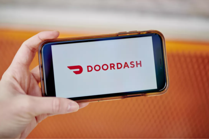 Cell phone being held in someones hand with the DoorDash app open
