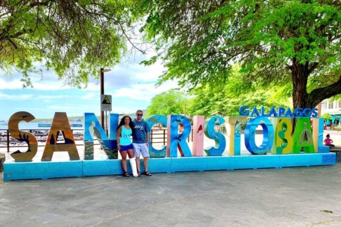 Couple standing in front of San Cristobal Galapagos Island sign. Girl with a broken leg.