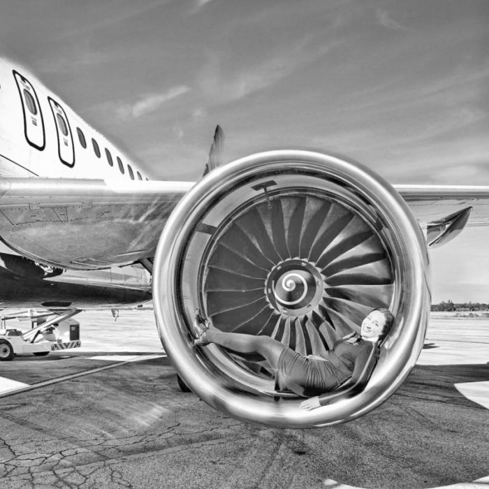 Woman posing laying on an airplane engine
