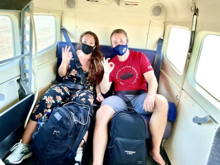 Couple sitting in back of smalll plane