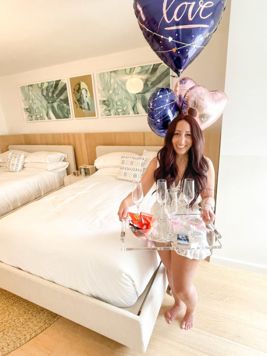 Girl holding tray of champagne glasses with bachelorette pins and balloons