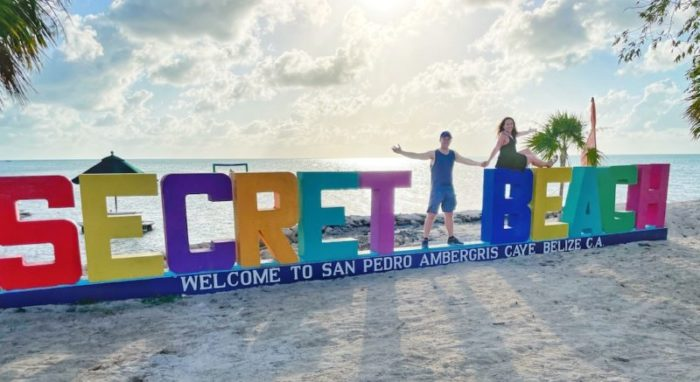 Couple posing with sign Secret Beach